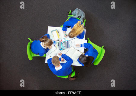 Overhead view of students doing their homework together - Stock Photo