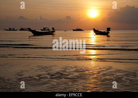 Thai fishing boats silhouetted against sunset, island Ko Tao / Koh Tao, part of the Chumphon Archipelago in Southern - Stock Photo
