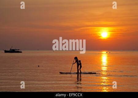 Mother and child standup paddleboarding, silhouetted against sunset, island Ko Tao / Koh Tao, Chumphon Archipelago, - Stock Photo