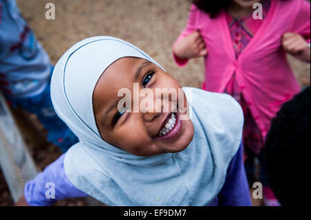 Happy Smiling muslim girl in headscarf in the playground of Primary school in London W2 - Stock Photo