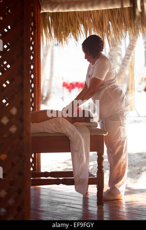 Woman giving a female customer body massage - Stock Photo