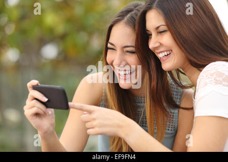 Two funny women friends laughing and sharing social media videos in a smart phone outdoors - Stock Photo