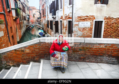 A view of an older woman sitting on the bridge in the city and begging for money in Venice, Italy, - Stock Photo