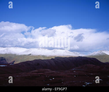 Storm & shower clouds passing over  snow capped summit of Helvellyn from near Ash Crags on High Raise above Grasmere - Stock Photo