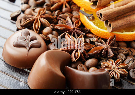 Fragrant spices, coffee and chocolate sweets on a dark striped background - Stock Photo