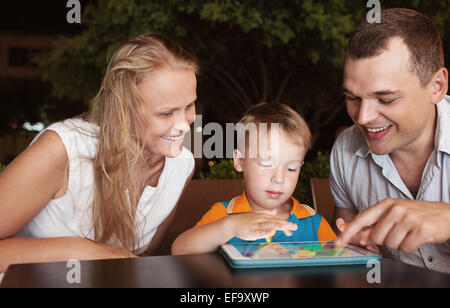 Family of three spending time in cafe with tablet computer - Stock Photo