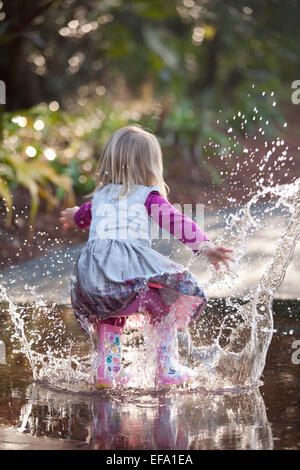 A little girl wearing rain boots splashes in a puddle on the street. - Stock Photo