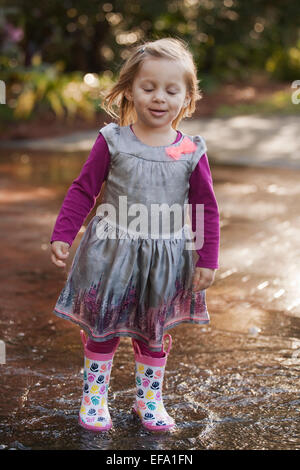 A little girl wearing rain boots, splashes in a puddle. - Stock Photo