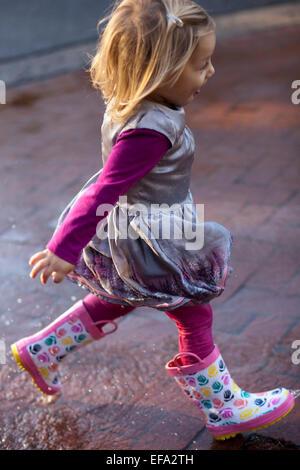 A little girl wearing rain boots runs through puddles. - Stock Photo