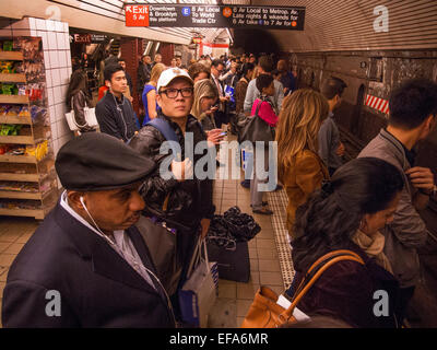 Multiracial passengers wait for a train on a subway station platform in New York City. Note signs. - Stock Photo