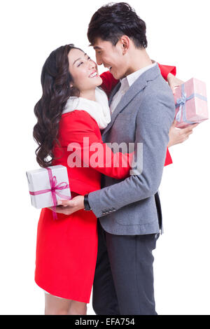 Happy young couple exchanging gifts - Stock Photo
