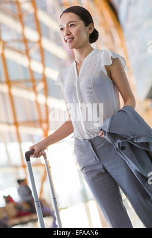 Young businesswoman walking in airport with suitcase - Stock Photo