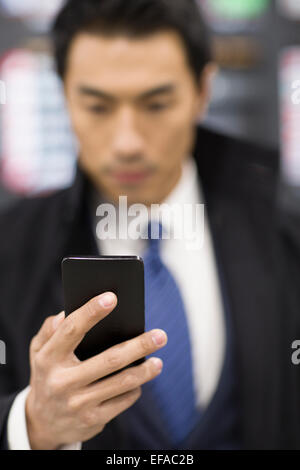 Young businessman using smart phone in airport - Stock Photo