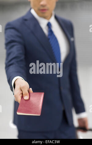 Young businessman showing his passport in airport - Stock Photo
