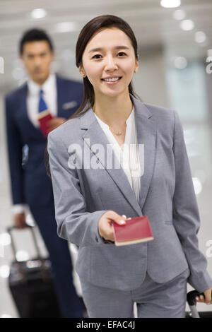 Young businesswoman showing her passport in airport - Stock Photo