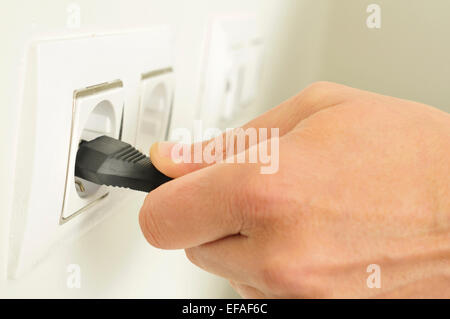 closeup of the hand of a man plugging in or unplugging an electrical plug in a socket - Stock Photo