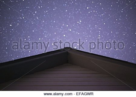 Stars above house's rooftop - Stock Photo