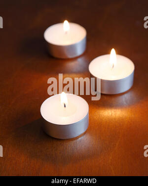 Three white, lit tea candles forming a triangle on a dark, brownish, wooden table.