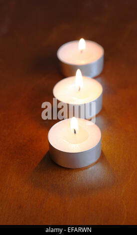 Three white, lit tea candles in line on a dark, brownish, wooden table.