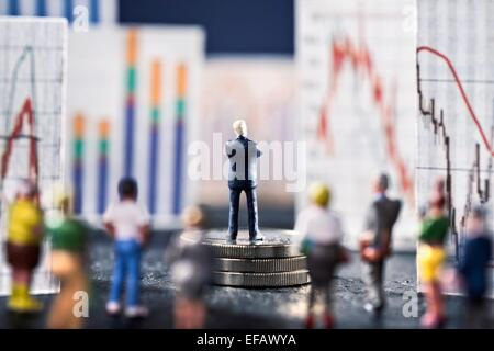 Banker looks on boards with various charts, symbolizing the ups and downs in the markets. He stands on a base of - Stock Photo