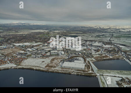 An aerial view over the Fishmoor Reservoir showing the Shadsworth Industrial Estate in Blackburn on a snowy winter - Stock Photo