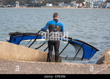 wind surfer carrying his sail board into the sea at Sandbanks, Poole in March - Stock Photo