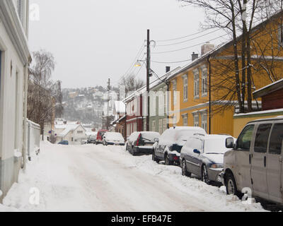 Winter in Vålerenga, Oslo Norway, small old wooden paneled houses snow in streets and walkways, challenging street - Stock Photo