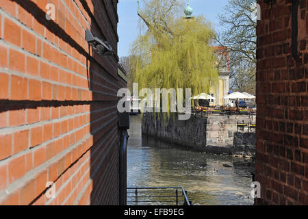 View through a gap between the walls from the historic mill buildings at the river Ilmenau and an open-air pub, - Stock Photo