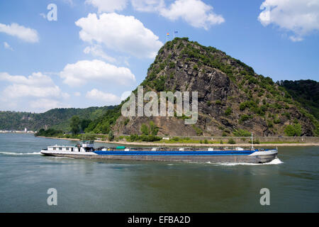 Cargo ship on the Rhine at the Lorelei rock, shale rock in the UNESCO World Heritage Upper Middle Rhine Valley near - Stock Photo