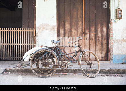 Old, rusty cyclo in front of a warehouse at a street in Myeik, Myanmar. - Stock Photo
