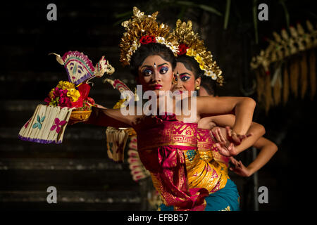 Young women performing a traditional Balinese dance on stage in Ubud, Bali - Stock Photo