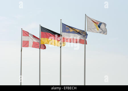 Flags of Denmark, Germany, Rostock and Scandlines in front of a blue sky at the port of Rostock - Stock Photo