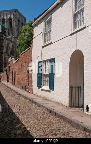 Under blue sky, view up cobbled, historic Chapter House Street with whitewashed house towards a tower of York Minster - Stock Photo