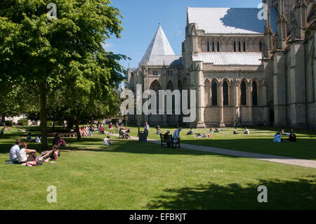 People sitting on the lawn, walking and relaxing in the summer sun in  scenic Dean's Garden by The Minster, York, - Stock Photo