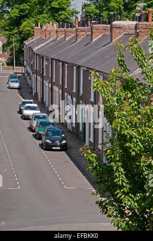View over rooftops of row of quaint attractive red brick Victorian terraced houses (cottages) & cars parked on road - Bishophill, York, England, UK.