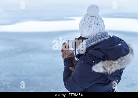 Young Asian woman in winter clothes seen from behind as she checks a photo on her smartphone in front of a frozen - Stock Photo