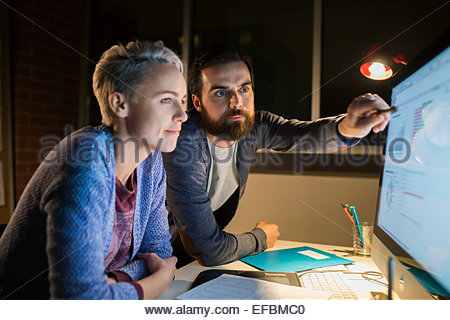 Graphic designers working late at computer in office - Stock Photo