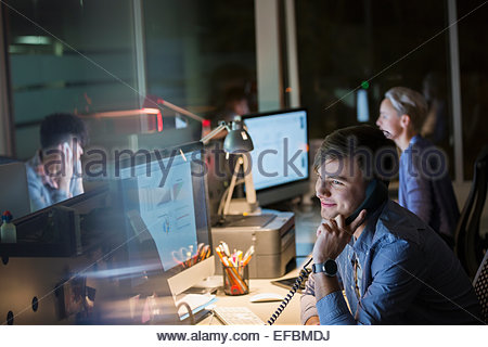 Businessman on cell phone working late in office - Stock Photo