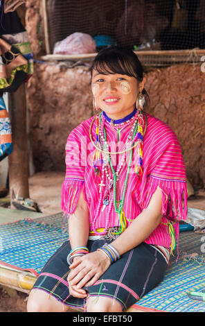 Young woman with traditional pierced ear lobes and necklaces and sun screen in Karen Padong village, Chiang Rai, - Stock Photo