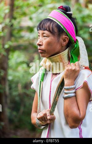 Long neck Burmese woman at Karen Padong village near Chiang Rai, Thailand. The village houses refugees from Myanmar - Stock Photo