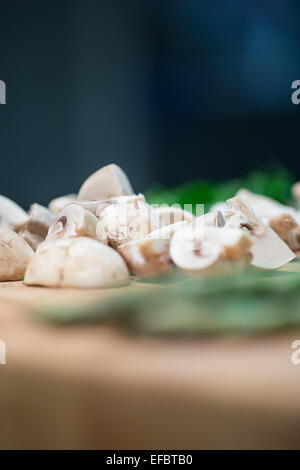 Mushrooms and green on Chopping Board - Stock Photo