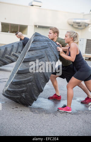 Close up of team flipping large tires outdoor - Stock Photo