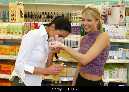 Freundinnen beim Shopping, Einkaufen im Supermarkt, testen Parfuem, Frei für Werbung (Modellfreigabe) - Stock Photo