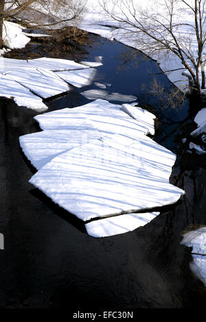 breaking white ice covering river on sunny day - Stock Photo