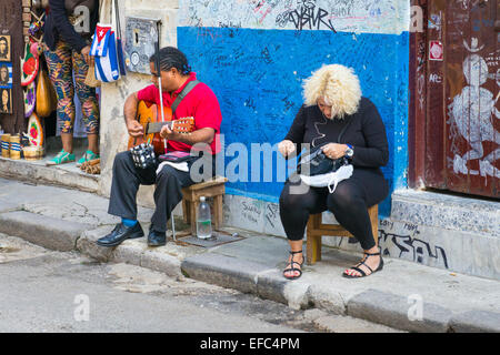 Cuba Old Havana La Habana Vieja blind man on stool begs begging plays guitar busker busking blond girl handbag by - Stock Photo