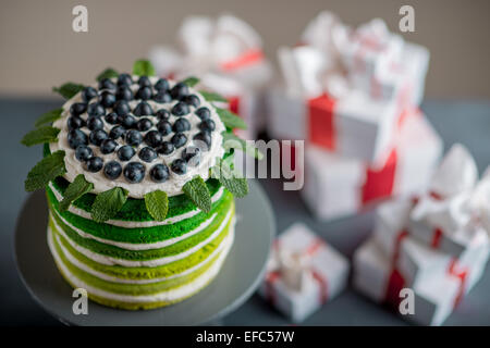 Nice sponge happy birthday cake with mascarpone and grapes with on the cake stand with gift boxes on festive light - Stock Photo