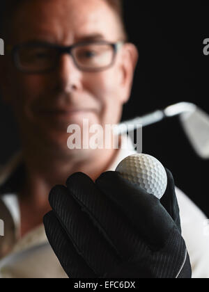 Close up, mature man golfer wearing a white shirt and he holds a golf ball on hand, iron golf club on his shoulder - Stock Photo