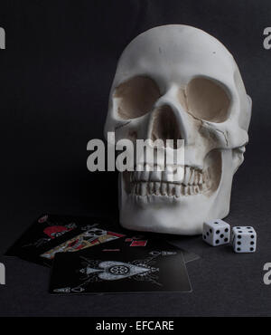 A skull with two die and black playing cards - Stock Photo