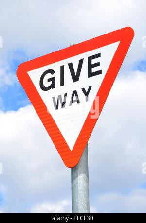 Detail of give way sign against blue sky - Stock Photo