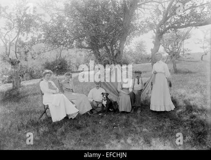 Antique 1903 photograph, family group under apple trees in Troy, New Hampshire, USA. - Stock Photo